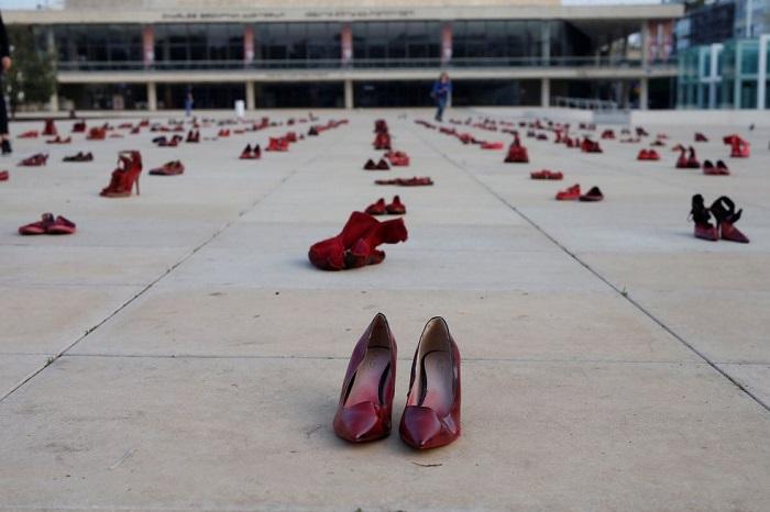Пустая красная обувь напоминает о том, что в мирное время массово убивают женщин.
