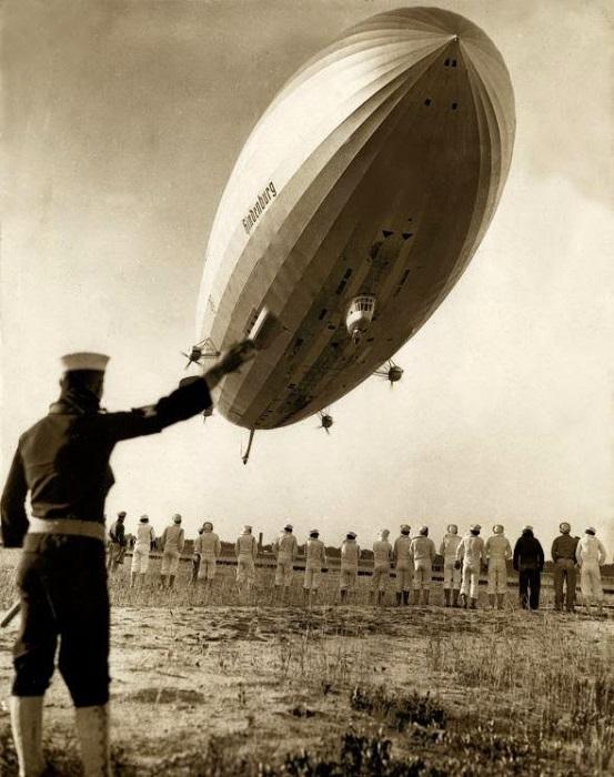 Американский работник ангара регулирует причаливание немецкого дирижабля, 1936 г.
