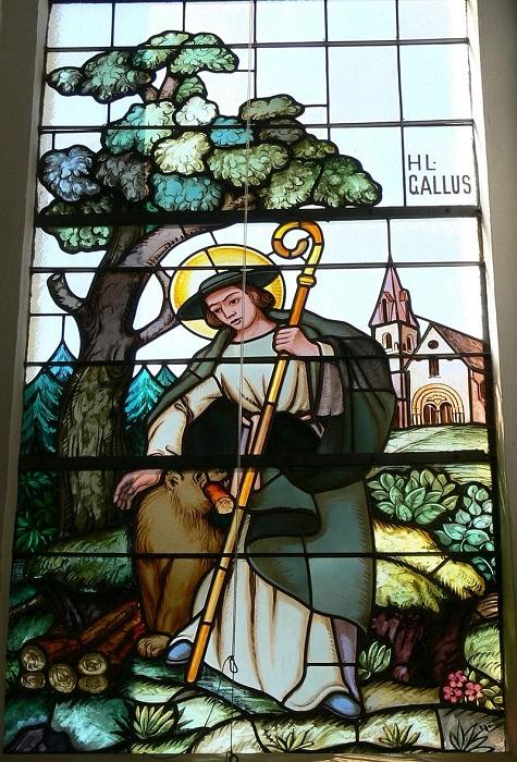 Этот витраж напоминат сцены из жизни собачников, но изображает святого Галла с медведем.