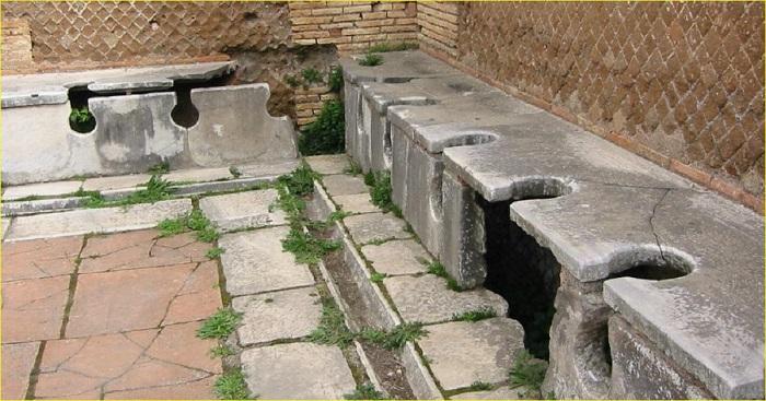 Общественные туалеты Древнего Рима были не для интровертов. Обратите внимание на отверстие под сиденьем - именно через него, с помощью насаженной на палку губки, специальный раб помогал клиентам навести чистоту.