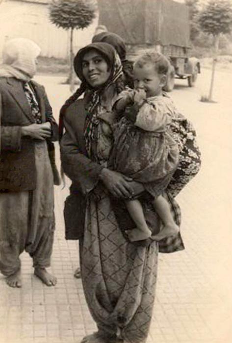 Фотография греческой цыганки со светловолосым ребёнком на руках середины двадцатого века.
