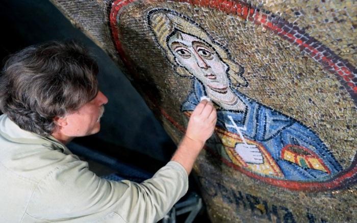 Реставратор очищает мозаику от пыли и копоти. /Фото:ukrinform.com