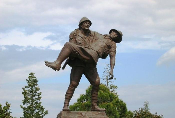 Турецкий солдат, который переносит раненого противника к его окопам.
