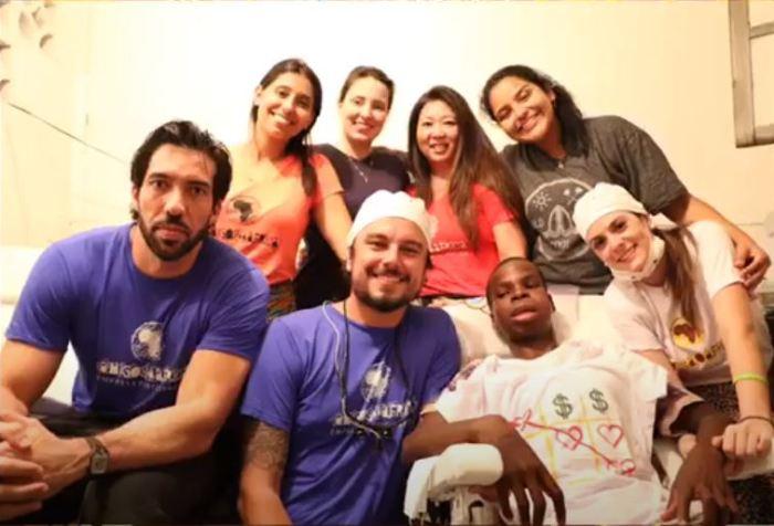 Молодой врач и его команда сфотографировались вместе с юным пациентом. /Кадр из видеорепортажа на сайте организации Рor1sorriso.