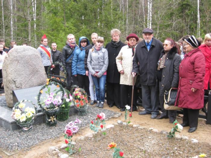 Единственный выживший в 1942-м узник детского гетто вместе с местными жителями у памятника погибшим детям. /Фото:proshkolu.ru