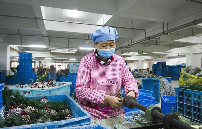 Работница китайского предприятия в Иу собирает искусственную ёлку.