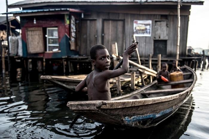 Мальчик плывет по  трущобам Макоко в Лагосе, которые прозвали «Африканской Венецией». Здесь живут тысячи горожан. /Фото: Мохаммед Эльшами