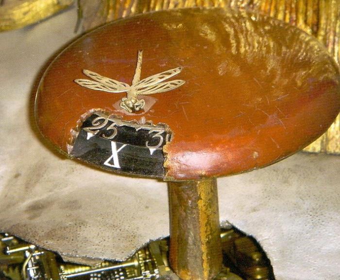 За золотым великолепием часов трудно разглядеть собственно циферблат: он находится на шляпке самого большого гриба