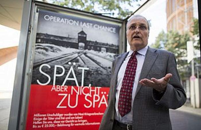 Эфраим Цурофф, глава Центра Симона Визенталя, беседует с журналистами, стоя перед плакатом с надписью «Операция Последний шанс-поздно, но не слишком поздно», Берлин, 2013 года (AP Photo/Gero Breloer)