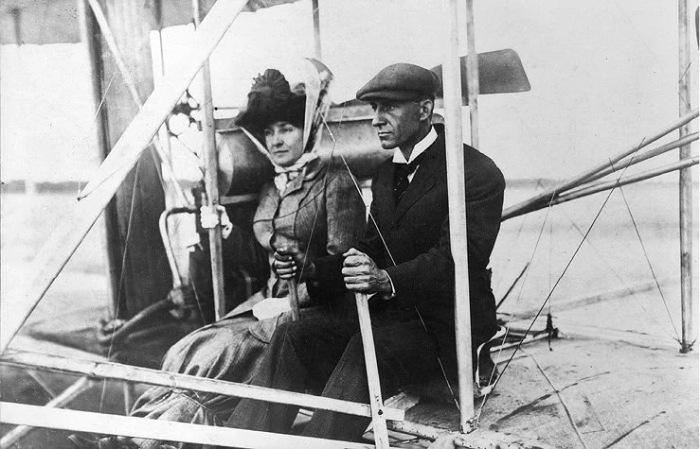 Эдит Берг в юбке, перевязанной веревкой, с Уилбором Райтом на аэроплане. Сентябрь 1908 года