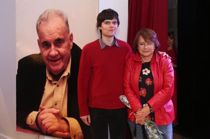 Ольга Рязанова с сыном у портрета Эльдара Рязанова. / Фото: www.womanhit.ru