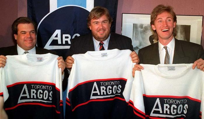 Брюс Макнолл, Джон Кэнди и Уэйн Гретцки демонстрируют свои новые майки «Торонто Аргонавтс» в феврале 1991 после того, как было объявлено, что они купили команду Канадской футбольной Лиги. / Фото: www.cponline.thecanadianpress.com