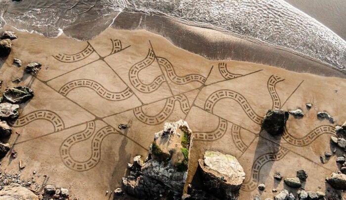 Волна смывает картину на песке / Фото: pikabu.ru