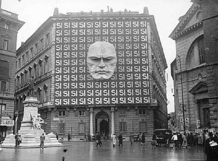 Фасад Палаццо Браски (в то время штаб-квартира Национальной фашистской партии) в Риме с агитационным плакатом во время политической кампании 1934 года. На плакате изображено лицо Муссолини с много раз повторяющимся словом «да» / Источник: Wikimedia Commons