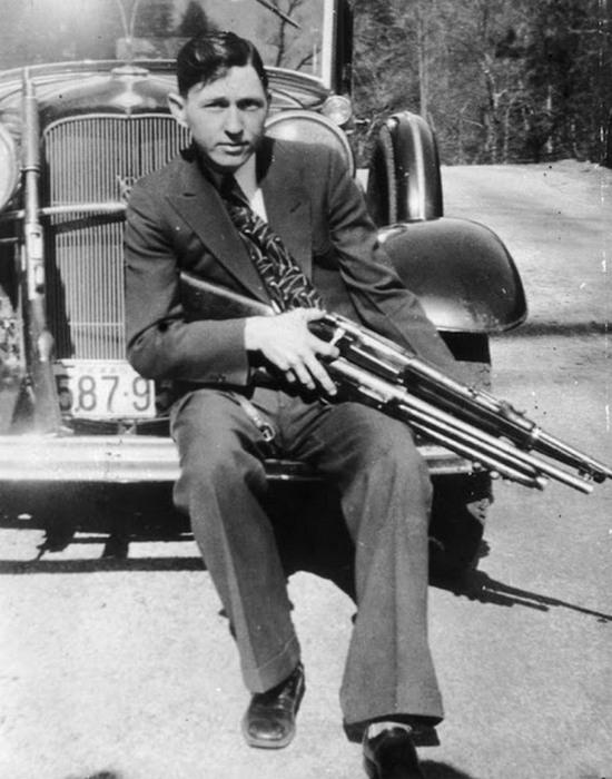 Клайд Бэрроу держит винтовку и дробовик, 1933 год.