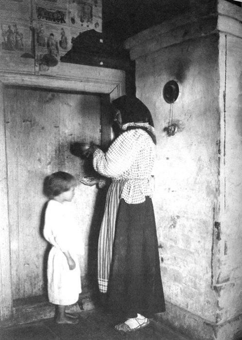 Знахарка лечит ребенка наговоренной водой.