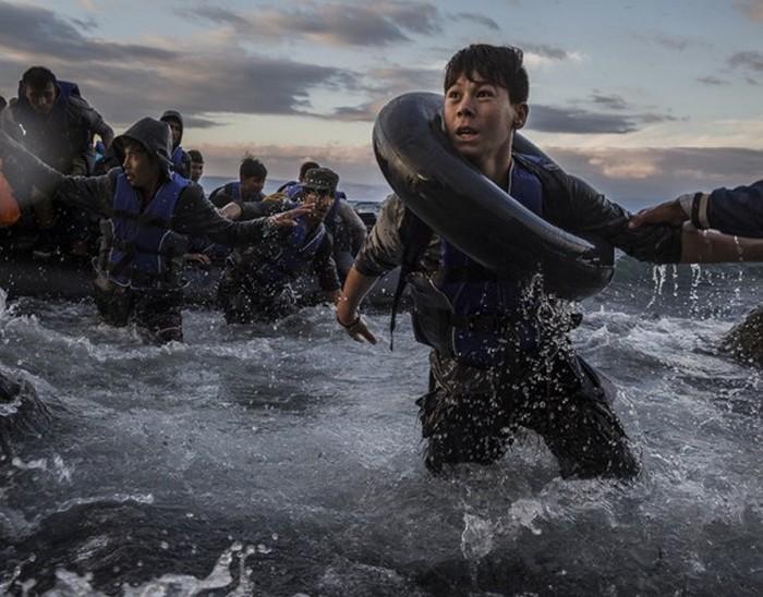Беженцы, приплывшие на резиновом плоту из Турции, высаживаются в шторм на берег острова Лесбос. Опасаясь того, что плот опрокинется или разорвется на острых камнях возле берега, некоторые из них начали прыгать в холодную воду, чтобы добраться до земли. (The New York Times / Тайлер Хикс - 1 октября 2015)