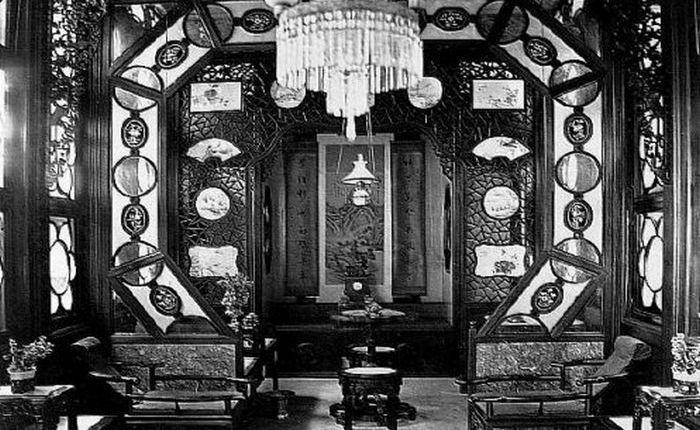 Роскошный и богато оформленный номер для курения опиума в так называемой Цветочной Лодке, которую можно было снять на ночь в Жемчужной Реке. На заднем фоне видна кровать, на которой предлагалось расслабиться курильщику. 1880 год.
