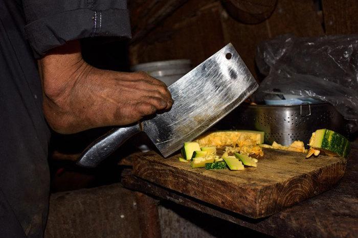 Чэнь ловко рубит дрова, варит суп, чистит кукурузные початки.