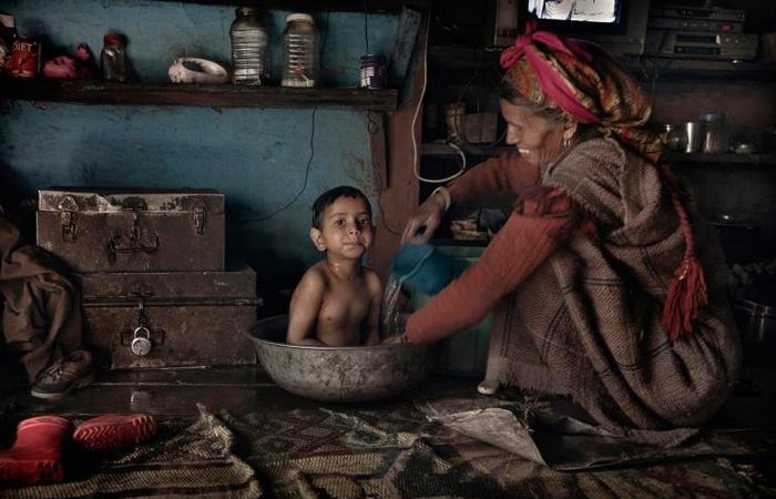 Местная жительница купает внука в тазике.