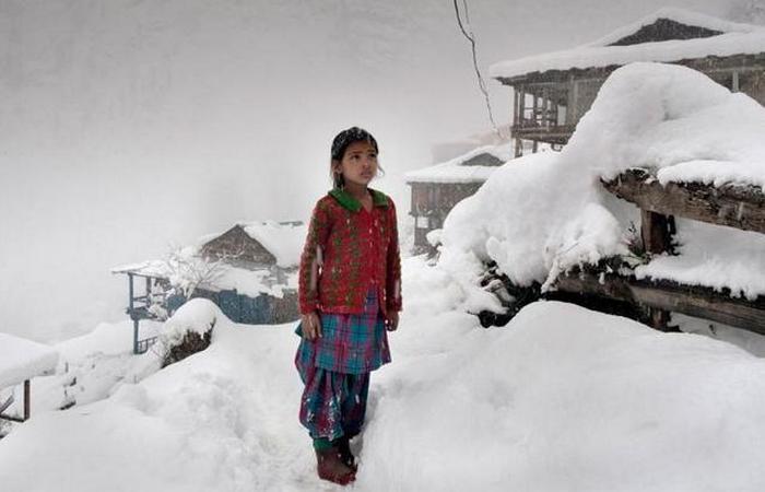 Местная девушка смотрит на горные вершины после большого снегопада, который привел к отключению электричества в ее родном селе.