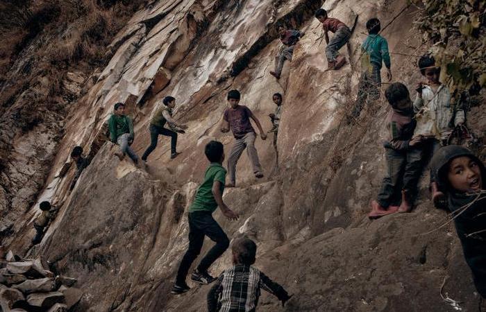 Деревенские дети, играющие на крутой скале на окраине деревни. Обычно в местных семьях много детей.