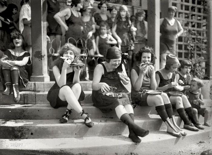 Одни из первых суфражисток в 1921 году, которые едят пиццу на ступеньках общественного здания.