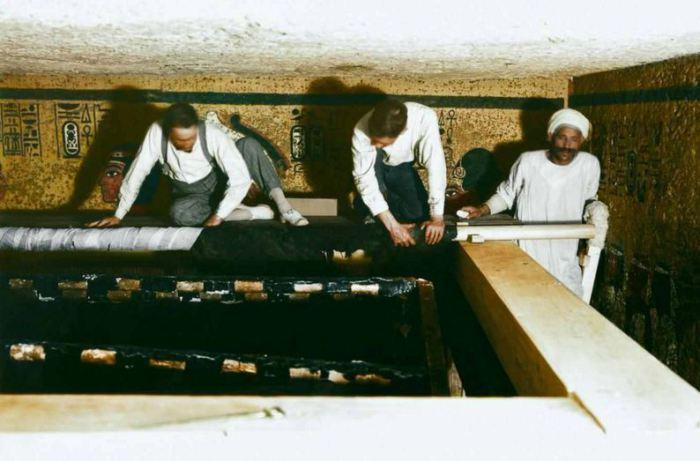 Картер и египетские рабочие сворачивают верхний покров с саркофага.
