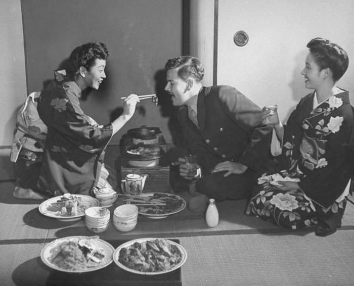 Гейша кормит посетителя с помощью традиционных палочек.