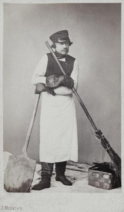 Дворник с метлой, лопатой и корзиной для мусора.