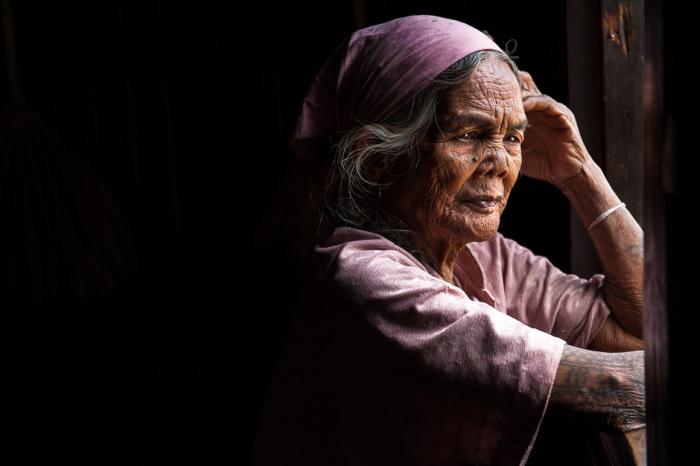 Женщина народности калинга задумчиво смотрит в окно. Татуировки на руках используются как украшения, а также свидетельствуют о принадлежности к определенному племени.