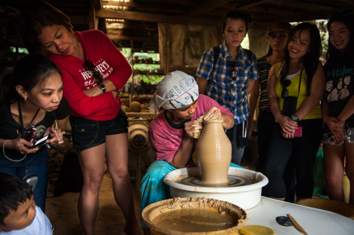 Туристы из Манилы смотрят, как местный житель Сигрид лепит глиняный кувшин.