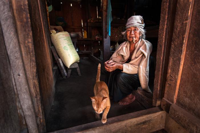 Игоротская женщина (племя тинггуан), которая курит в своем доме.