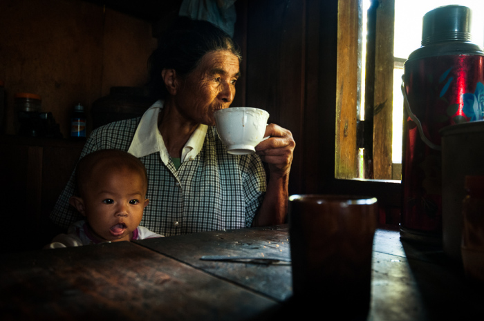Канканайская женщина с внуком пьет кофе во время полуденного перерыва от работы в рисовом поле.
