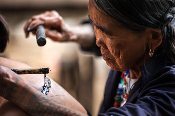 Фанг-од делает татуировку местному туристу из Манилы. Она использует шип дерева помело, прикрепленный к куску бамбука. В качестве чернил выступает сажа, которую она собирает на дне своей кастрюли.