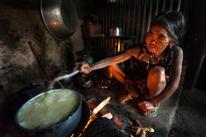 Фан-од в процессе готовки дома. После того, как она доест кашу из кастрюли, старушка выскребает сажу с ее дна для новых тату.