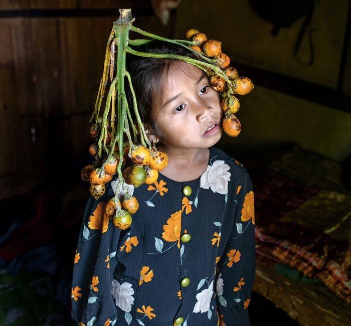 Аниша Нонгрум в головном уборе из плодов пальмы арека (которые больше известны, как жевательный бетель).
