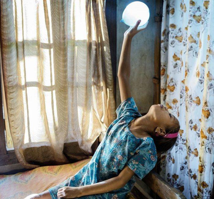 Старшая из трех братьев и сестер, девятилетняя Фида Нонгрум, играет с воздушным шариком в своей спальне. Однажды ее младшая сестра станет главой всей семьи.