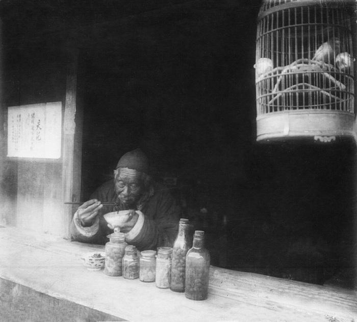 Пожилой человек обедает лапшой. Рядом в клетке видны птицы, пойманные им на продажу.