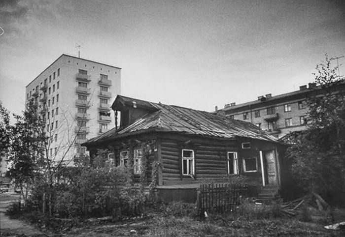 Опустевшая изба на фоне городских построек.