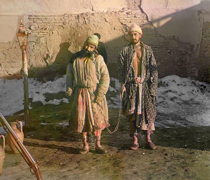 Двое заключённых, скованных цепью.