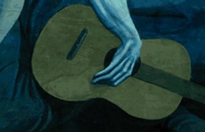 Гитарист находит утешение среди однообразия окружающего мира в гитаре.