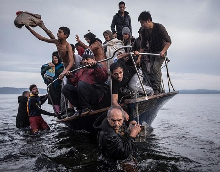 Турок на свой лодке высаживает беженцев недалеко от деревни Скала на греческом острове Лесбос. (The New York Times / Сергей Пономарев - 16 ноября 2015).