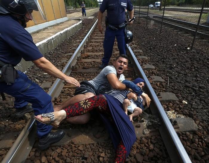 Венгерские полицейские стоят над семьей, которая бросилась на рельсы во время задержания на железнодорожном вокзале в городе Бичке. (Thomson Reuters / Ласло Балог - 3 сентября 2015)
