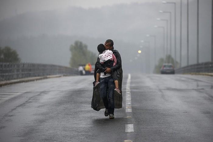 Сириец, целующий свою дочь, во время грозы на дороге. Фото сделано возле границы Греции с Македонией, недалеко от Идомени .(Thomson Reuters / Яннис Бехракис - 10 сентября 2015)