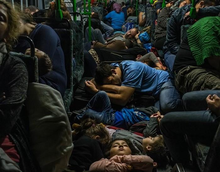 Ахмад Маджид (в синей футболке в центре) спит в проходе автобуса со своими детьми. Справа в зеленом свитере его брат Фарид Маджид, а также другие члены их семьи и десятки других беженцев. Фото сделано в автобусе, выехавшем из Будапешта в Вену. (The New York Times / Маурисио Лима - 5 сентября 2015)