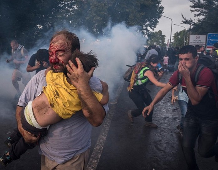 Мужчина пытается оградить своего ребенка от полицейских с дубинками и слезоточивым газом при пересечении границы в Хоргосе, Сербия. (The New York Times / Сергей Пономарев - 16 сентября 2015)
