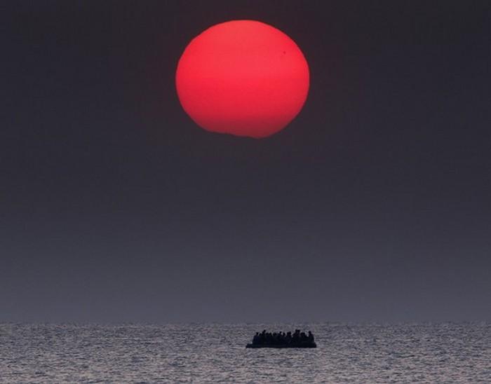Переполненная надувная лодка с сирийскими беженцами дрейфует в Эгейском море между Турцией и Грецией после поломки мотора возле греческого острова Кос. (Thomson Reuters / Яннис Бехракис - 11 августа 2015)