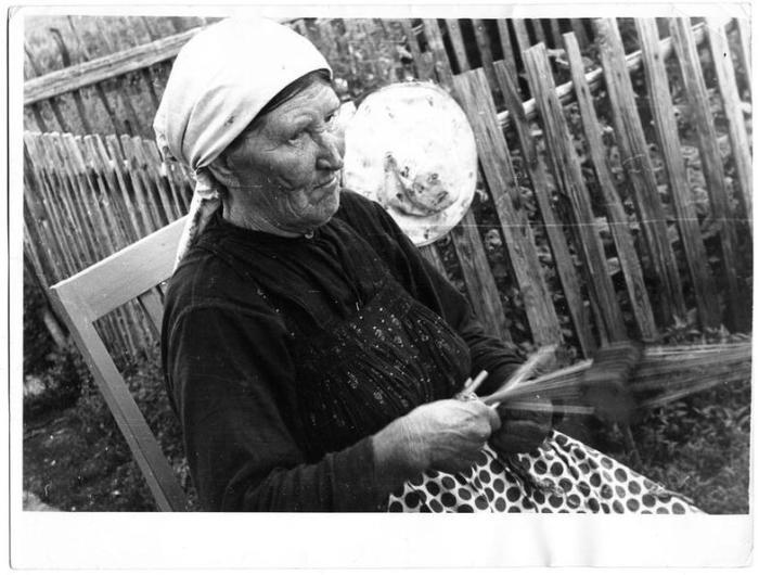 Жена Ивана Тарасьевича за плетением на плашках пояса.