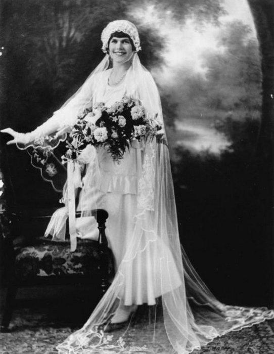 Невеста в атласном платье с косым подолом и вышитой вуалью